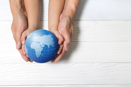 el mundo en tus manos: World concept: Two human hands holding global on wooden background.