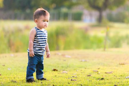 Glückliches Baby, das im Gras auf den Feldern steht. Smiling Kind im Freien