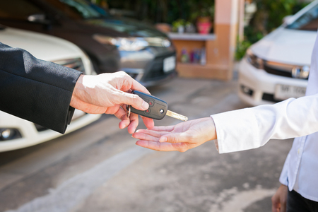 Salesman offering car key to a customers at showroom used car.