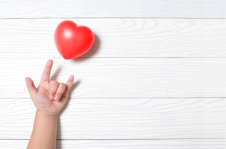 Hand kid supporting love symbol with heart on wooden background.