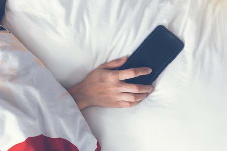 Hand sleeping and holding a mobile phone on the bed. vintage tone Stock Photo