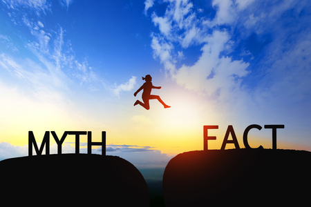 Woman jump through the gap between Myth to Fact on sunset. Stock Photo