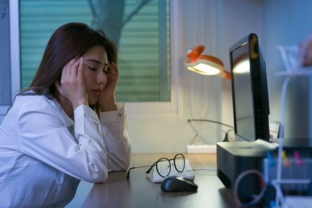 Young tired business woman headache sitting at computer in workplace.