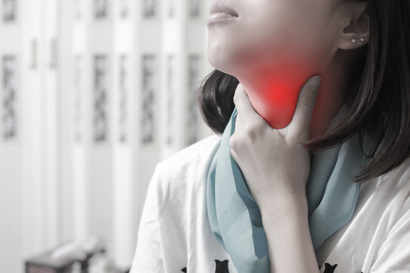 Sore throat of a asian women. Touching the neck.