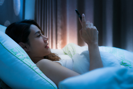 Woman on bed late at night texting using mobile phone tired falling sleep.