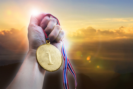 Businessman hand holding golden coin medal on hill.