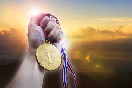 Main d'homme d'affaires tenant la médaille d'or sur la colline. Banque d'images - 92699531