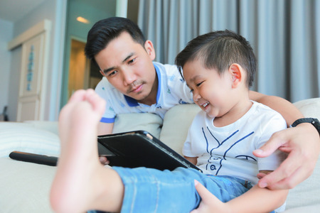 Father and his young son having fun by gaming on a tablet. Banque d'images