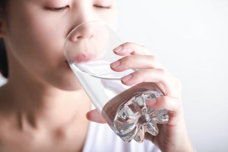 Giovane donna che beve acqua pulita in sua mano. Archivio Fotografico