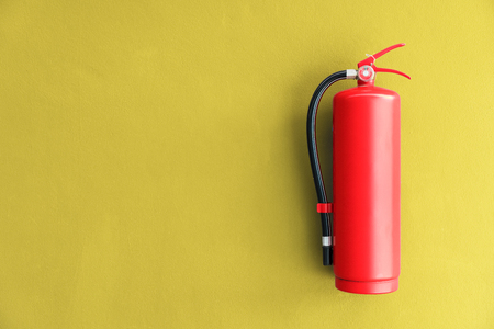 Fire extinguisher on the yellow wall background.
