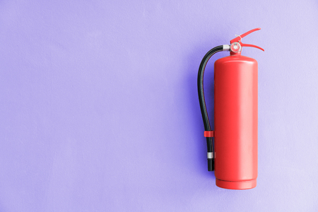 Fire extinguisher on the violet wall background. Stock Photo