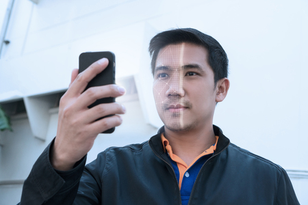 Biometric facial recognition on smartphone. Unlock smartphone as it scans his face. Stock Photo
