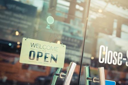 Ouvrez grand signe à travers la vitre de la porte du café. Ton vintage