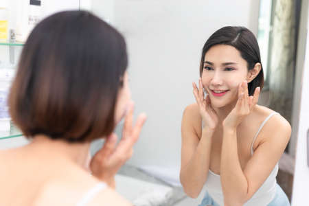 Beauty portrait of a smiling beautiful woman applying face cream. Stockfoto