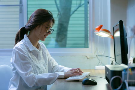 Young woman working on co-working home at night.