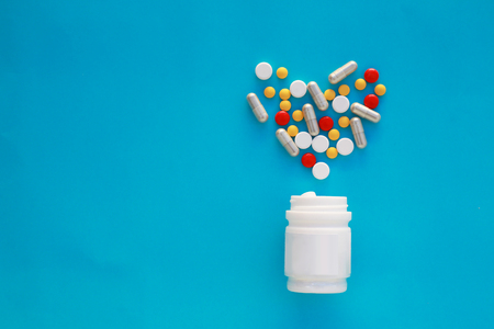 Pills heart out of pill bottle on blue background, top view Stock Photo