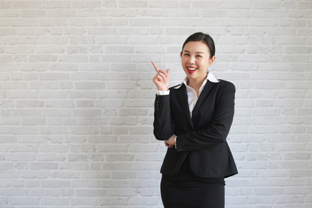 Young beautiful businesswoman smiling looking at camera pointing finger in side over white background. 写真素材