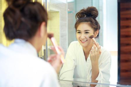 Beautiful young asian woman in bathrobe applying makeup.