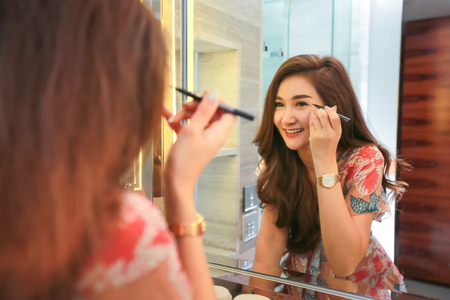 Woman getting ready for work doing morning makeup routine putting mascara in bathroom. Banque d'images