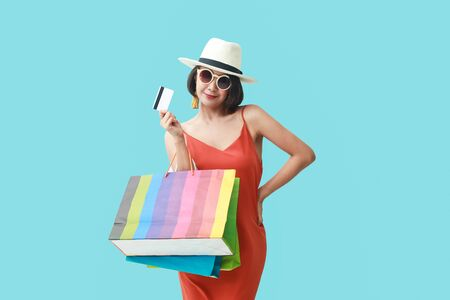 Portrait of asian girl wearing dress and sunglasses holding shopping bags. Stok Fotoğraf