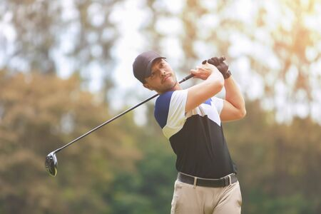 Male golf player on professional golf course. Taking a shot.