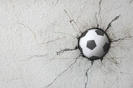 Sport soccer ball coming in cracked wall with grunge texture.