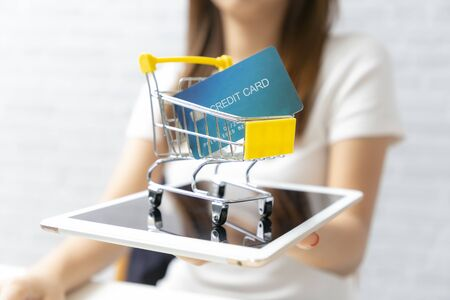 Businesswomen holding shopping cart contains credit card on tablet.