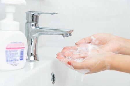 Woman hand press pure white plastic pump bottle and take cleaner foam. Banco de Imagens