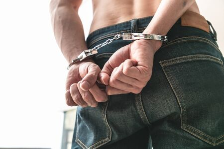 Man with his back hands handcuffed in criminal concept.