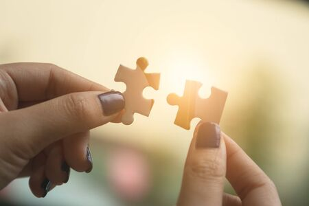 Businesswoman hand connecting jigsaw puzzle at outdoor. Business success and strategy concept