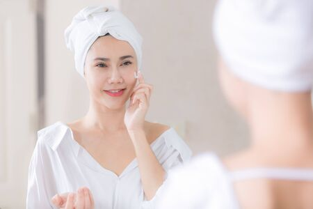 Young asian woman applying foundation or moisturizer on her face in front of mirror.