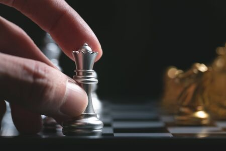 Human hand moving Silver King chess piece at table.