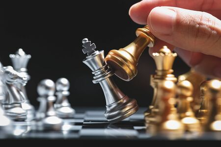 Hand of man moving gold chess battle figure in competition success play.
