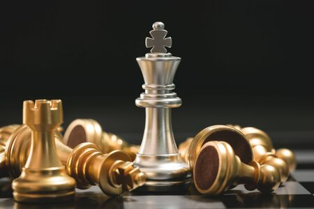Human hand moving dark King chess piece at table