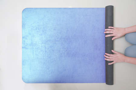Hands of Woman rolling her Yoga mat after a workout. top view, copy space