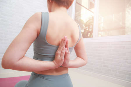 Young woman practicing yoga with namaste behind the back. Stockfoto