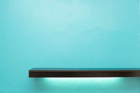 Empty white shop shelf, retail shelf with light under the shelf on blue background. Stockfoto