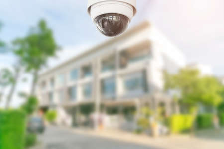 Security CCTV camera with home on background. Stock Photo