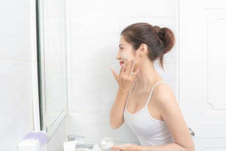 Close up asian  beautiful woman applying face cream. Stockfoto