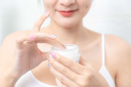 A woman holds a moisturizer in her hand and her skin and wrinkle from impurities.