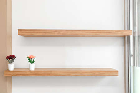 Flowers in a vase on a wooden shelfs, Wooden shelves on the wall.