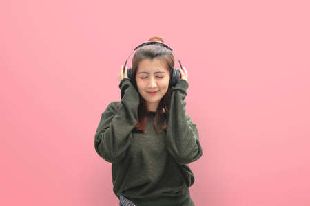 Beautiful young woman in headphones listening to music and dancing on pink background.