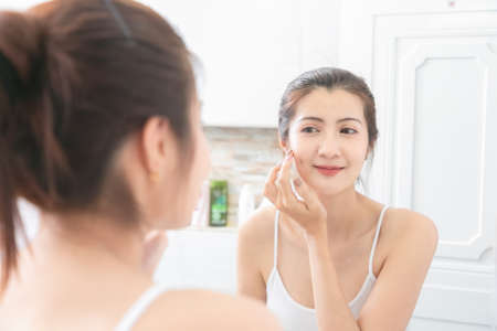 Asian Beauty Woman apply cream on her face in bathroom.