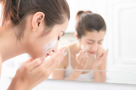Young beauty woman washing her face in bathroom. Stockfoto