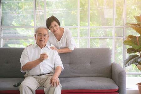 Happy asian elderly couple in love drinking milk togetherness at the living room. Healthy food concept.