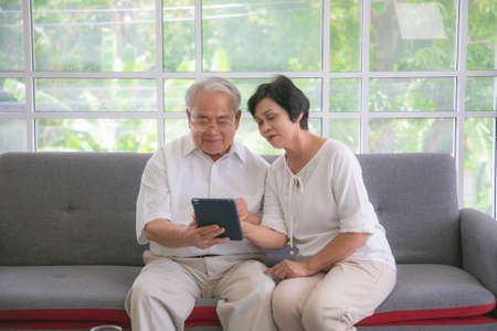 Couple of seniors smiling and looking at the same tablet on the sofa.