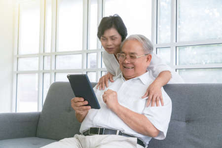 Couple of seniors smiling and looking at the same tablet hugged on the sofa. Stockfoto