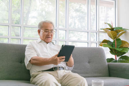 Senior asian man sitting on sofa and reading new on his tablet computer.