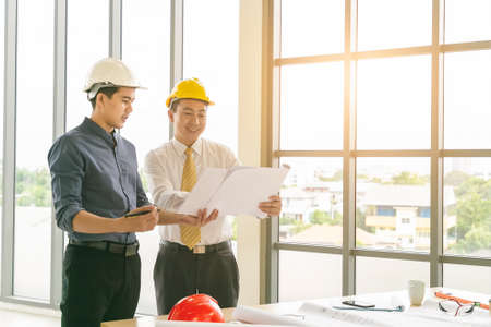 Professional two engineers are discussing the new project. The senior man is standing and holding the blueprint. Stockfoto