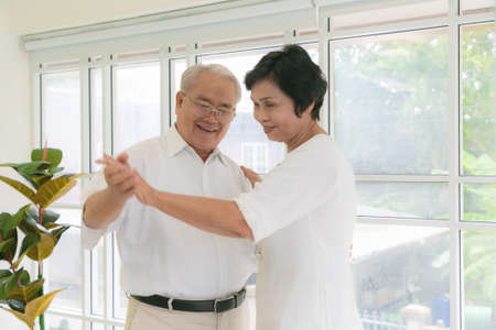 Asian couple senoir dancing together while listen to music in living room. Stockfoto